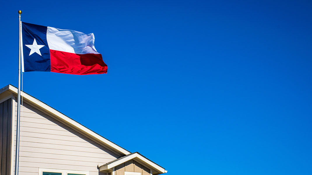 Texas state flag flying over a house, against a blue sky