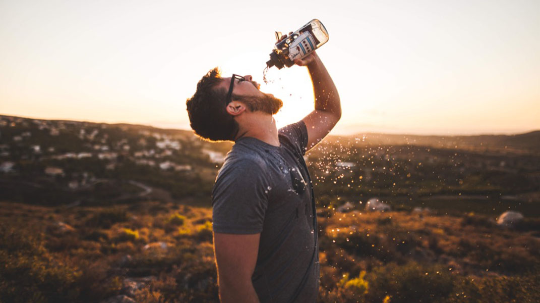 Man drinking from a reusable water bottle